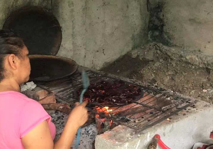 roasting a variety of dried chiles on a comal (skillet) prior to making the sauce