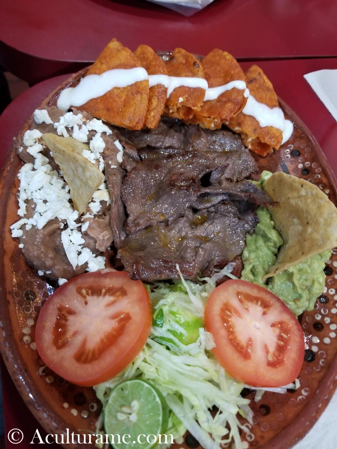 Traditional Enchiladas Potosinas with cecina, guacamole and refried beans.
