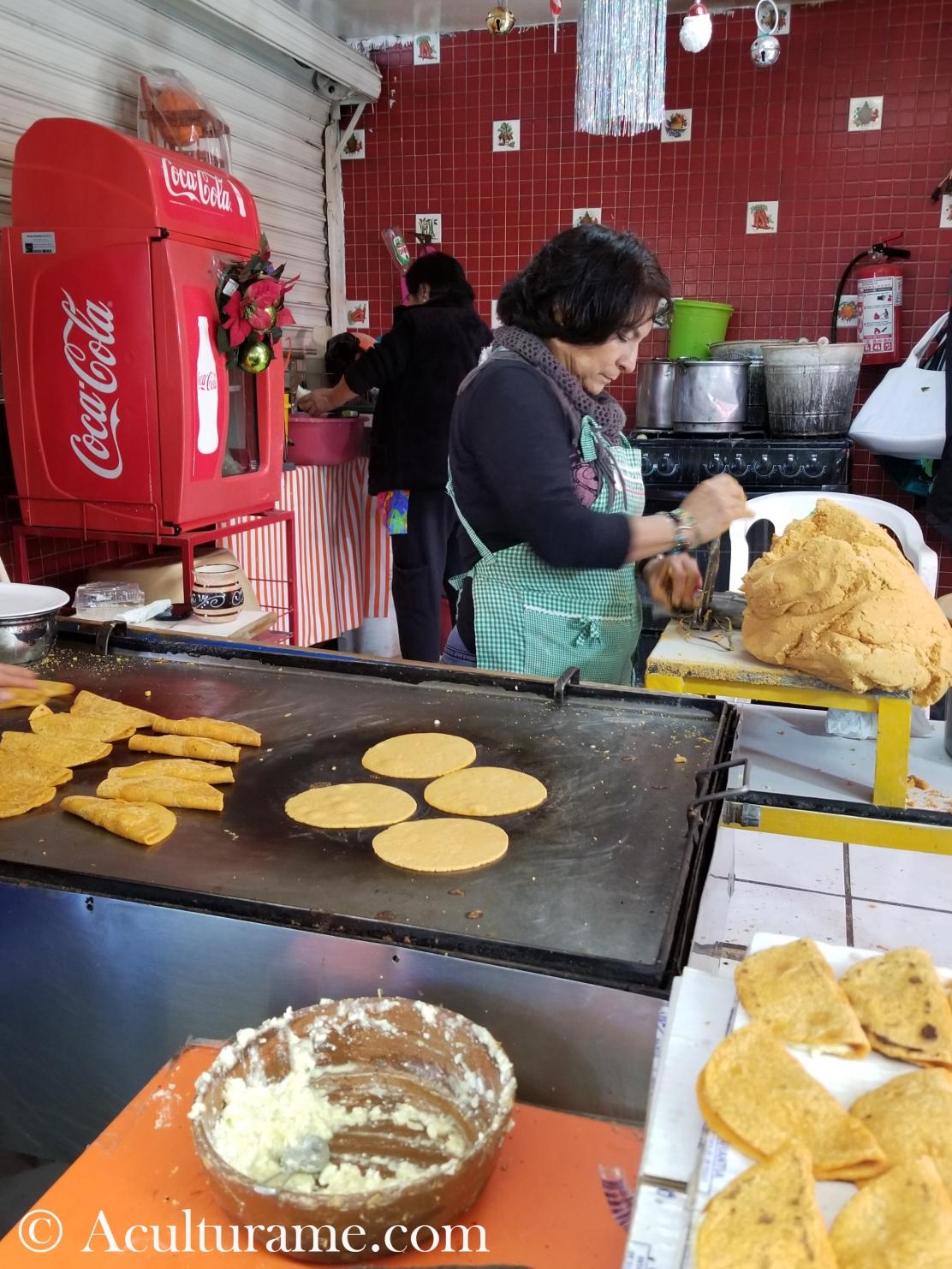 A woman preparing traditional enchiladas potosinas from scratch.